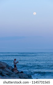 Itajai, Santa Catarina / Brazil - 07 25 2018: fisherman stands on breakwater rocks while the Moon rises