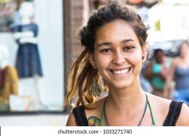 Itajai, Santa Catarina, Brazil - February 22th, 2018: A female brazilian street bracelets vendor, with tatoo and piercing in her face smiling at streets near the Port of Itajai.