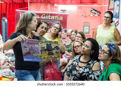 Itajai, Santa Catarina, Brazil - February 22th, 2018: A female teacher is showing a magazine with knitting crochet patterns to her pupils in a knitting course at La Gitana store.