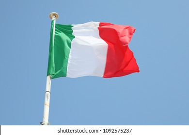 italia flag on a mat in the wind and blue sky
