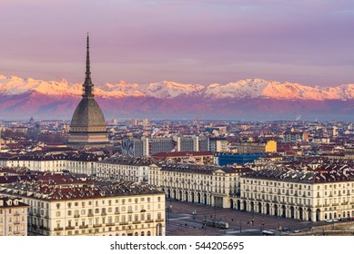 Italia: Torino skyline (Turin, Italy), cityscape at sunrise with details of the Mole Antonelliana towering over the city. Scenic colorful light on the snowcapped Alps in the background.