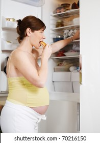italian 6 months pregnant woman standing near refrigerator and eating fat food. Waist up, vertical shape, side view