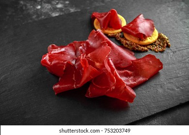 italian air-dried salted bresaola beef thinly sliced and served on stone board. Perfect appetizer.