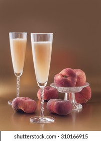Italian alcoholic cocktail Bellini prosecco with peach in champagne flute glass on the dark gold background vertical