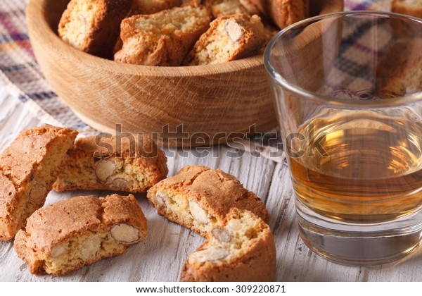 Italian almond biscotti biscuits and sweet wine in a glass closeup on the table. Horizontal