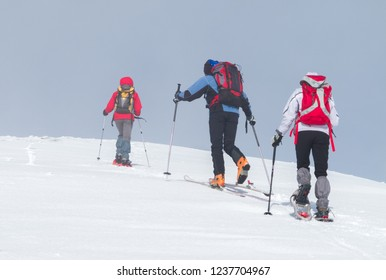 Italian Alps: group of hikers backpackers snowshoeing and ski mountaineering ascending snowy slopes. Photos with Snow