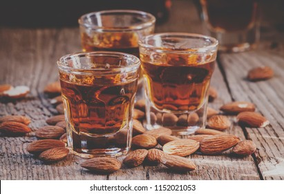Italian amaretto liqueur with dry almonds on the old wooden background, selective focus and toned image