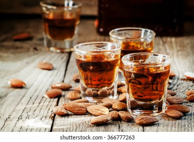 Italian amaretto liqueur with dry almonds on the old wooden background, selective focus