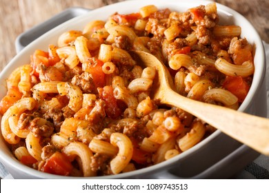 Italian American goulash with pasta, beef and tomatoes close-up in a saucepan. horizontal