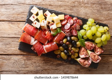 Italian antipasti from cheese, prosciutto ham, grapes, figs, sausages and olives close-up on a wooden table. horizontal top view from above