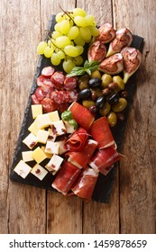 Italian antipasti from cheese, prosciutto ham, grapes, figs, sausages and olives close-up on a wooden table. Vertical top view from above