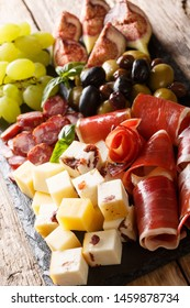 Italian antipasti from cheese, prosciutto ham, grapes, figs, sausages and olives close-up on a wooden table. vertical