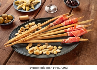 Italian antipasti. Grissini with parma ham and roasted almonds, with olives and artichokes, on a dark rustic wooden background