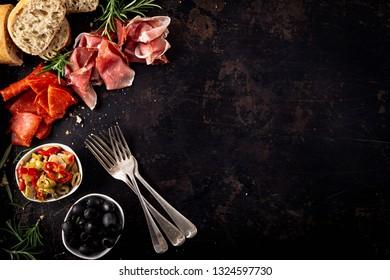 Italian antipasti with mediterranean olives, parma ham, salami and ciabatta bread