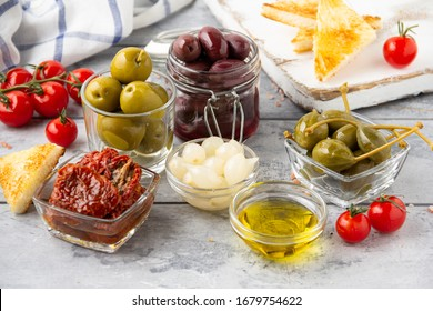 Italian antipasti, olives, capers, sun- dried tomatoes , olive oil, bread (ciabatta, baguette, croutons). Mediterranean assortment of delicious food, wine snacks