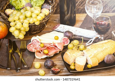 Italian antipasti plate with ham, salami, cheeses, olives and figs and wine