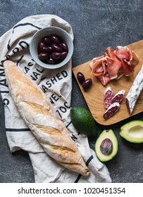 Italian antipasti snacks set. Assorted Italian food set. Chopping board with meat, olives, avocado and baguettes. Top view
