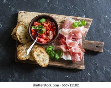 Italian antipasti - tomato bruschetta and prosciutto on a wooden cutting board on dark background, top view. Wine snacks