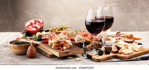 Italian antipasti wine snacks set. Cheese variety, Mediterranean olives, pickles, Prosciutto di Parma, pepper and salami