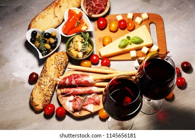 Italian antipasti wine snacks set. Cheese variety, Mediterranean olives, crudo, Prosciutto di Parma, salami and wine in glasses over stone grunge background