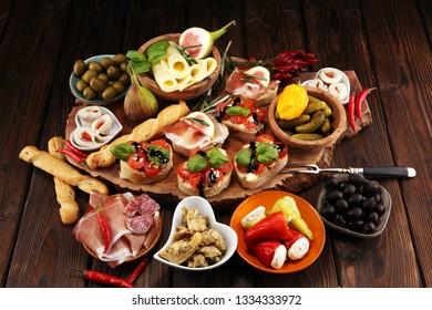 Italian antipasti wine snacks set. Cheese variety, Mediterranean olives, pickles, Prosciutto di Parma, tomatoes, artichokes on table