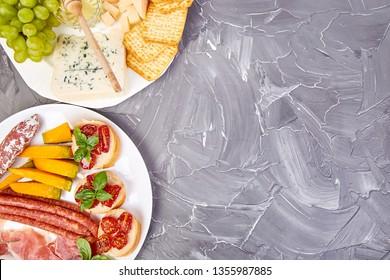 Italian antipasti wine snacks set. Antipasto catering platter with, salami, cheese , grapes,, Prosciutto Brushettas on grunge grey background. Italian food. Mediterranean. Falt lay. Copy space