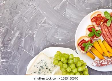 Italian antipasti wine snacks set. Antipasto with jerky, salami, cheese , grapes, olives, pickles melon, Brushettas on grunge grey background. Italian food. Mediterranean. Falt lay Copy space