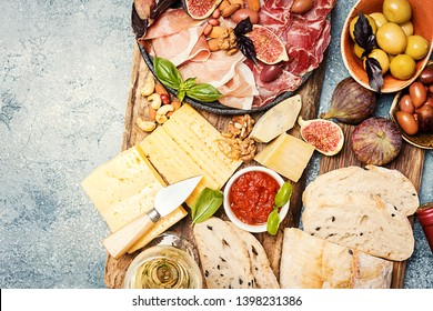 Italian antipasti wine snacks set. Cheese variety, nuts, Mediterranean olives, sauces, Prosciutto di Parma or jamon, and wine over gray background, top view
