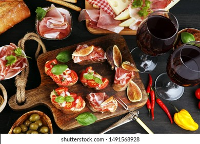 Italian antipasti wine snacks set. Cheese variety, Mediterranean olives, pickles, Prosciutto di Parma, tomatoes, artichokes on table