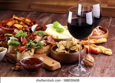 Italian antipasti wine snacks set. Cheese variety, Mediterranean olives, pickles, Prosciutto di Parma, tomatoes, artichokes and wine in glasses over black grunge background