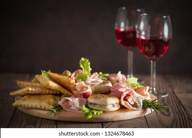 Italian aperitif - aperitivo: Crescentina modenese or tigelle, Gnocco fritto or Crescentina, salad, prosciutto, and wine. All products are made in Italy, Emilia-Romagna.