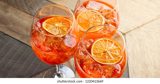 """Italian aperitif  """"aperol stpritz"""" with ice and a slice of orange in  large round glasses on a wooden table in a bar in Italy"""