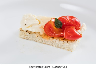 Italian aperitif bruschetta with tomatoes and cheese on white plate