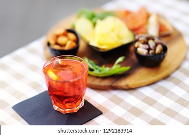 Italian aperitives/aperitif: glass of cocktail (sparkling wine with Aperol) and appetizer platter on the table. Traditional italian cuisine.