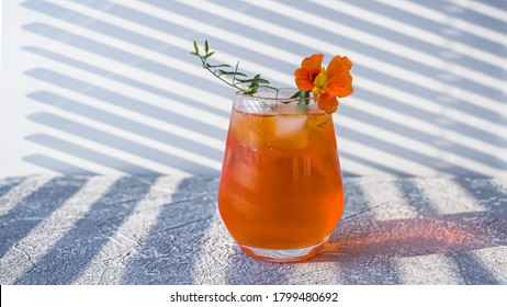 Italian Aperol Spritz alcohol cocktail with ice cubes. Summer refreshing orange drink with bitter, sparkling wine prosecco and soda garnished with edible flowers. Copy space for text