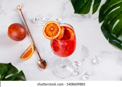 Italian Aperol Spritz cocktail with orange slices and ingredients on white stone table. Summer drink, homemade sangria. Copy space