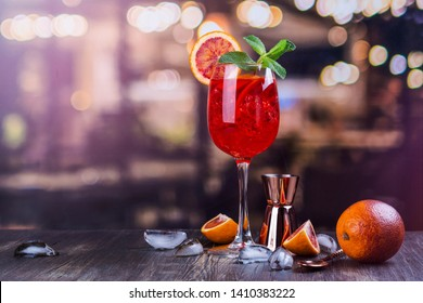 Italian Aperol Spritz cocktail with orange slices on a bar counter. Summer sangria or red cocktail with ingredients