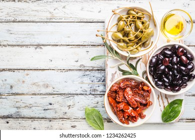 Italian appetizer from above. Mediterranean snack assortment. Black olives, capers, olive oil, and sun-dried tomatoes top view.