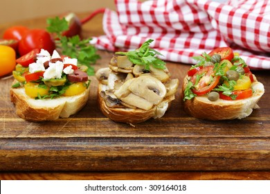 Italian appetizer bruschetta with tomatoes, olives, cheese and mushrooms