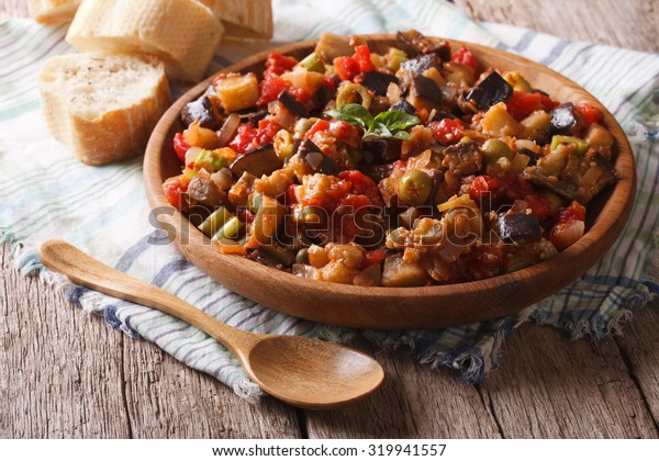 Italian appetizer Caponata with eggplants close-up on a wooden plate. Horizontal