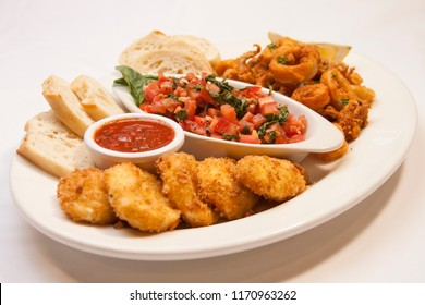 italian appetizer sampler platter featuring bruschetta with sliced baguette, deep fried calamari and breaded mozzarella cheese rounds with a ramekin of marinara sauce