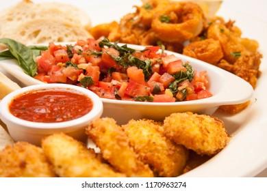 italian appetizer sampler platter featuring bruschetta with sliced baguette, deep fried calamari and breaded mozzarella cheese rounds with a ramekin of marinara sauce