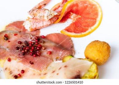 Italian appetizer with swordfish carpaccio, prawns, shrimp skewers and fried fish.