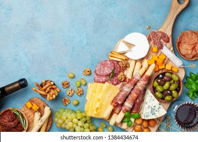 Italian appetizers or antipasto set with gourmet food on table top view. Mixed delicatessen of cheese and meat snacks with red wine.