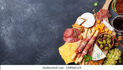 Italian appetizers or antipasto set with gourmet food on black stone table top view. Mixed delicatessen of cheese and meat snacks. Format of the banner.