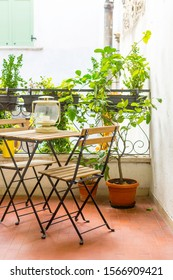 An Italian balcony with green potted plants and garden furniture. a table and chairs to enjoy the balmy evening.