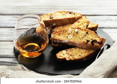 Italian biscotti cookies on black slate board and sweet wine Vin Santo. Fresh baked cookies with nuts and dried cranberries.