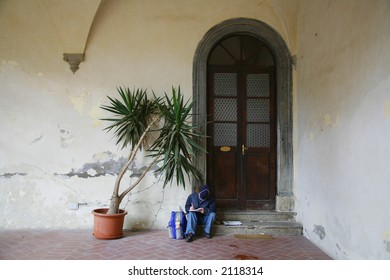 Italian boy doing his homework while waiting outside the house for his mother to come home.