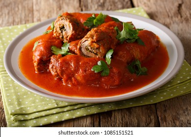Italian bracilole: tender beef stuffed with parsley and parmesan cheese in tomato sauce close-up on a plate on a table. horizontal