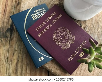 italian and brazilian passport leaning on a wooden table seen from above close up - dual citizenship
